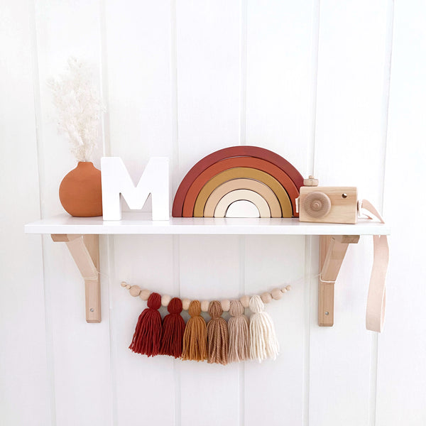 Nursery Shelf decorated with decor in earthy tones. The shelf has a terracotta vase, wooden toy, painted rainbow stacker toy and yarn tassel garland hanging below it.