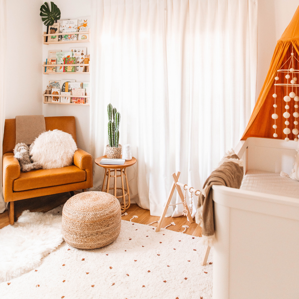 Image of the Hunter and Nomad Cotton rust dot rug. A cream-coloured rug featuring rust-coloured dots and cream tassels. The rug sits on the floor in a nursery, surrounded by neutral furniture and accessories.