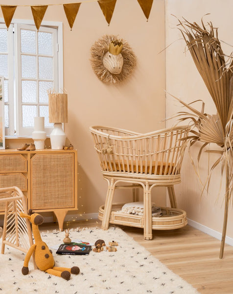 Image of Sacred Bundle Bassinet in the corner of a neutral toned nursery. The bassinet has rust-coloured bedding and is surrounded but other neutral furniture items and accessories.