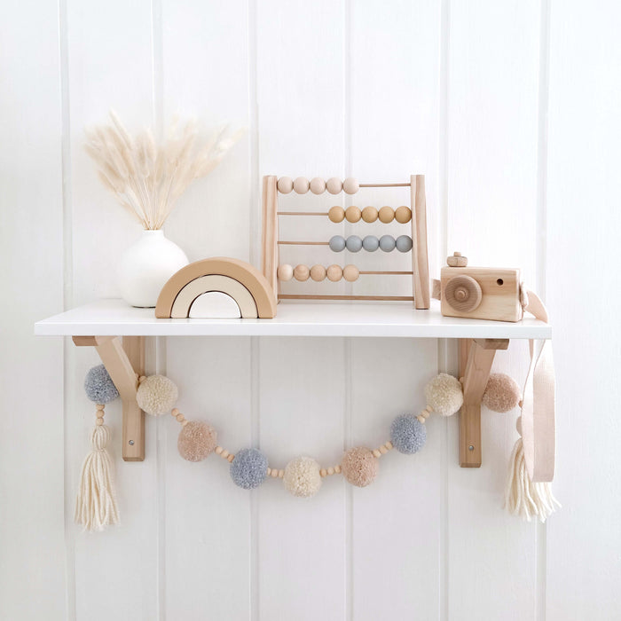 Boys nursery shelf with blue pom pom garland hanging. The shelf has a abacus, wooden camera and rainbow next to a white vase