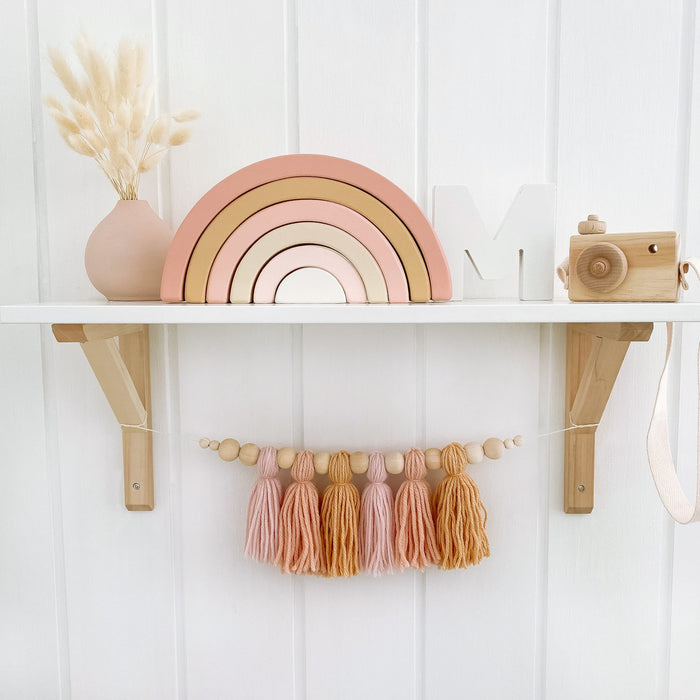 Styled nursery shelf with wooden toys and yarn tassel garland below. All decor is in pink tones