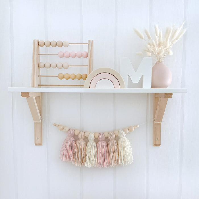 Girls styled nursery shelf. Wooden abacus with pink and beige beads, Matching wooden rainbow and vase with bunny tails. There is a matching yarn tassel garland below.