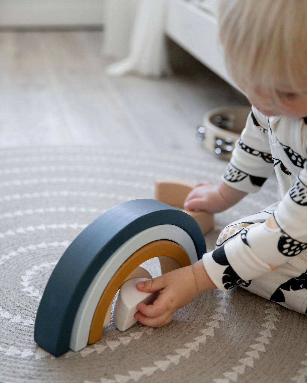 Boy playing with wooden rainbow stackable toy on bedroom floor.
