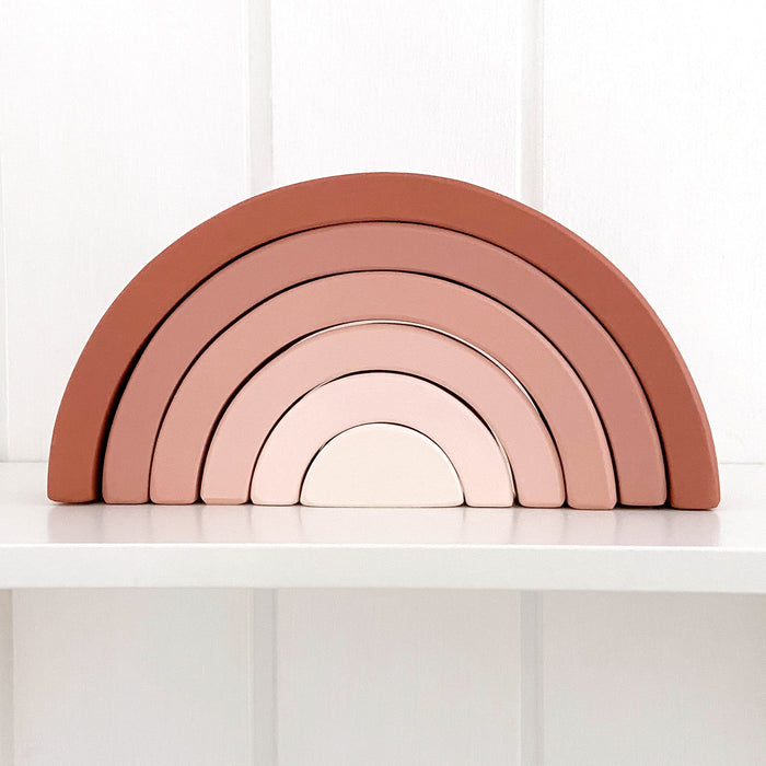 Earthy pink wooden rainbow stackable toy sitting on nursery room shelf. The rainbow is ombre in earthy pink tones.