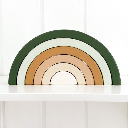 Boho wooden rainbow toy painted in green and mustard tones. The rainbow is sitting on a nursery shelf