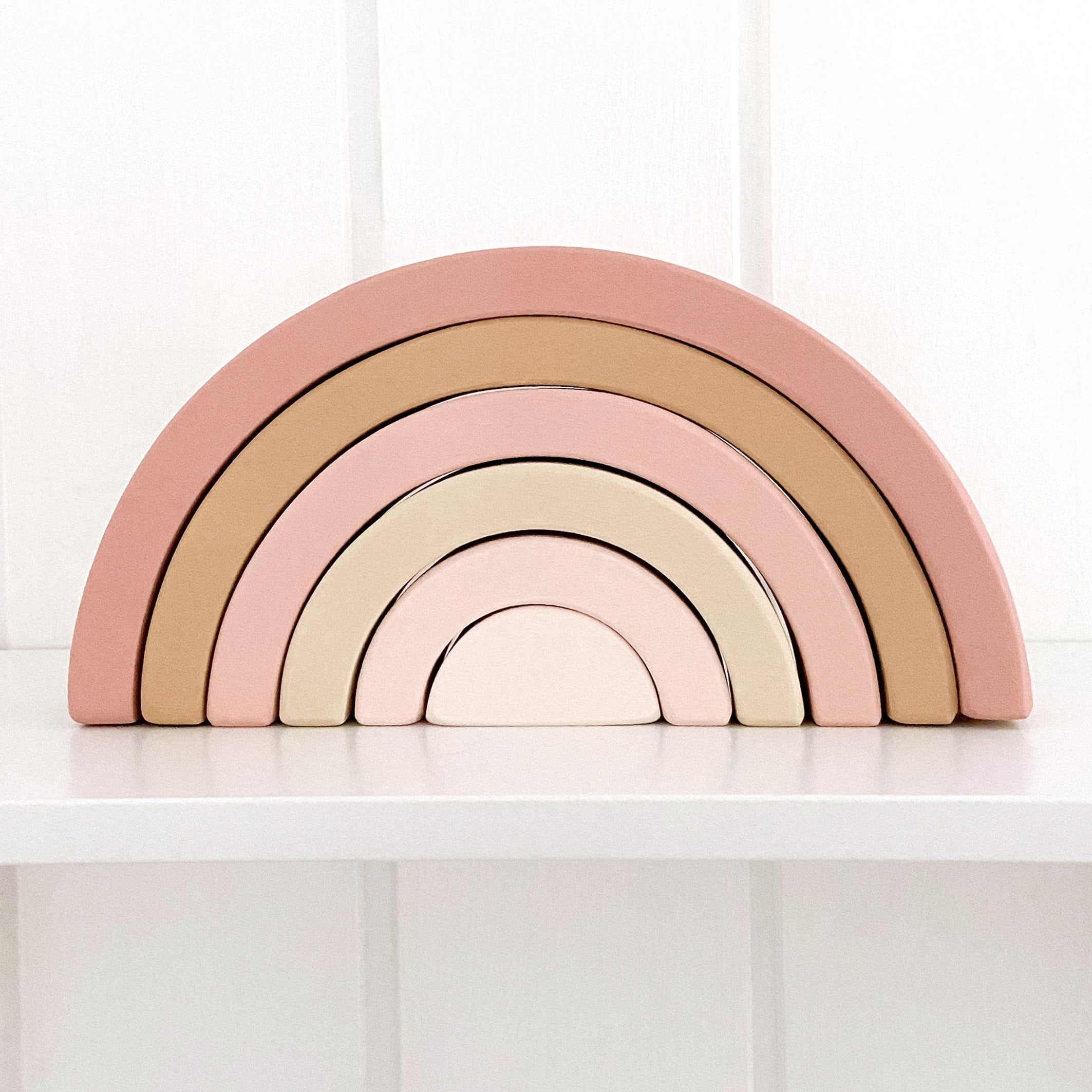 Boho wooden rainbow toy in pink and beige. Rainbow is sitting on a nursery shelf