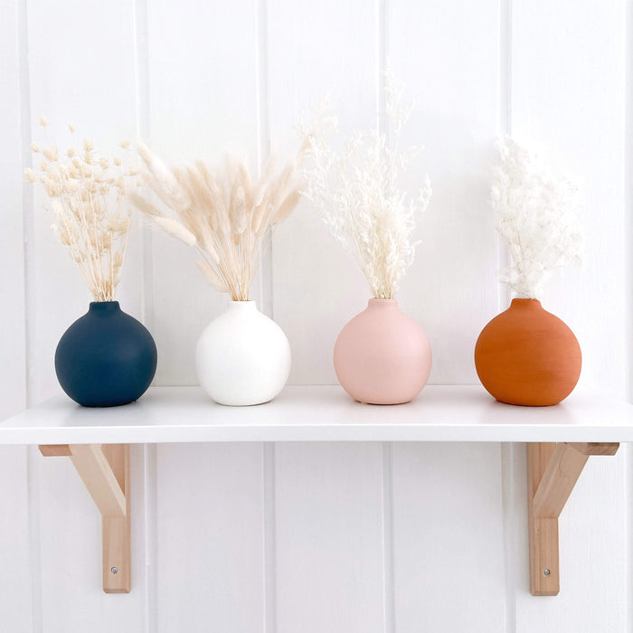 Four vases sitting on nursery shelf with dried flowers in each. The vases are small and round and in navy, white, pink and terracotta