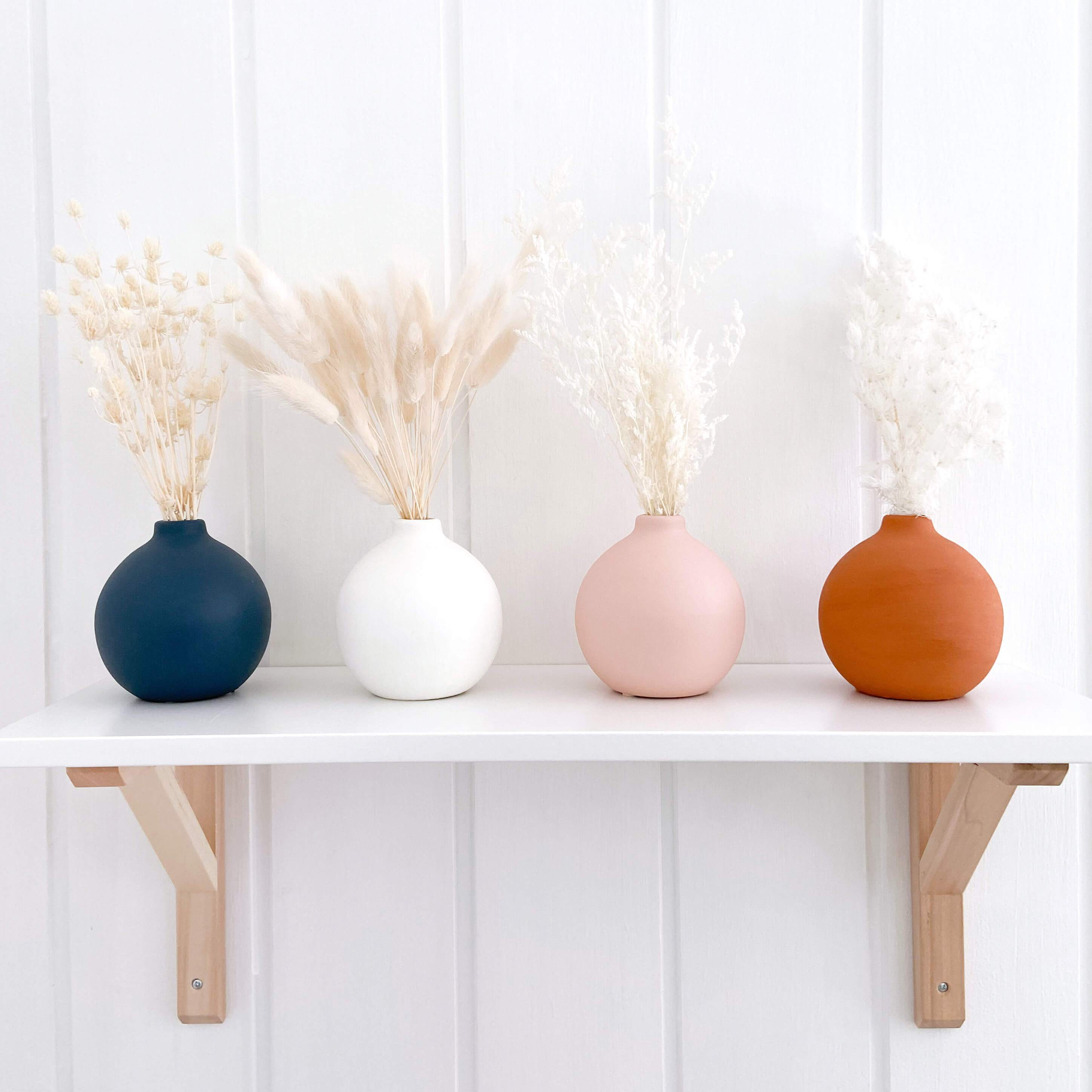 4 round ceramic hand painted vases in navy, pink, white and terracotta sitting on nursery shelf with dried flowers in each of the vases