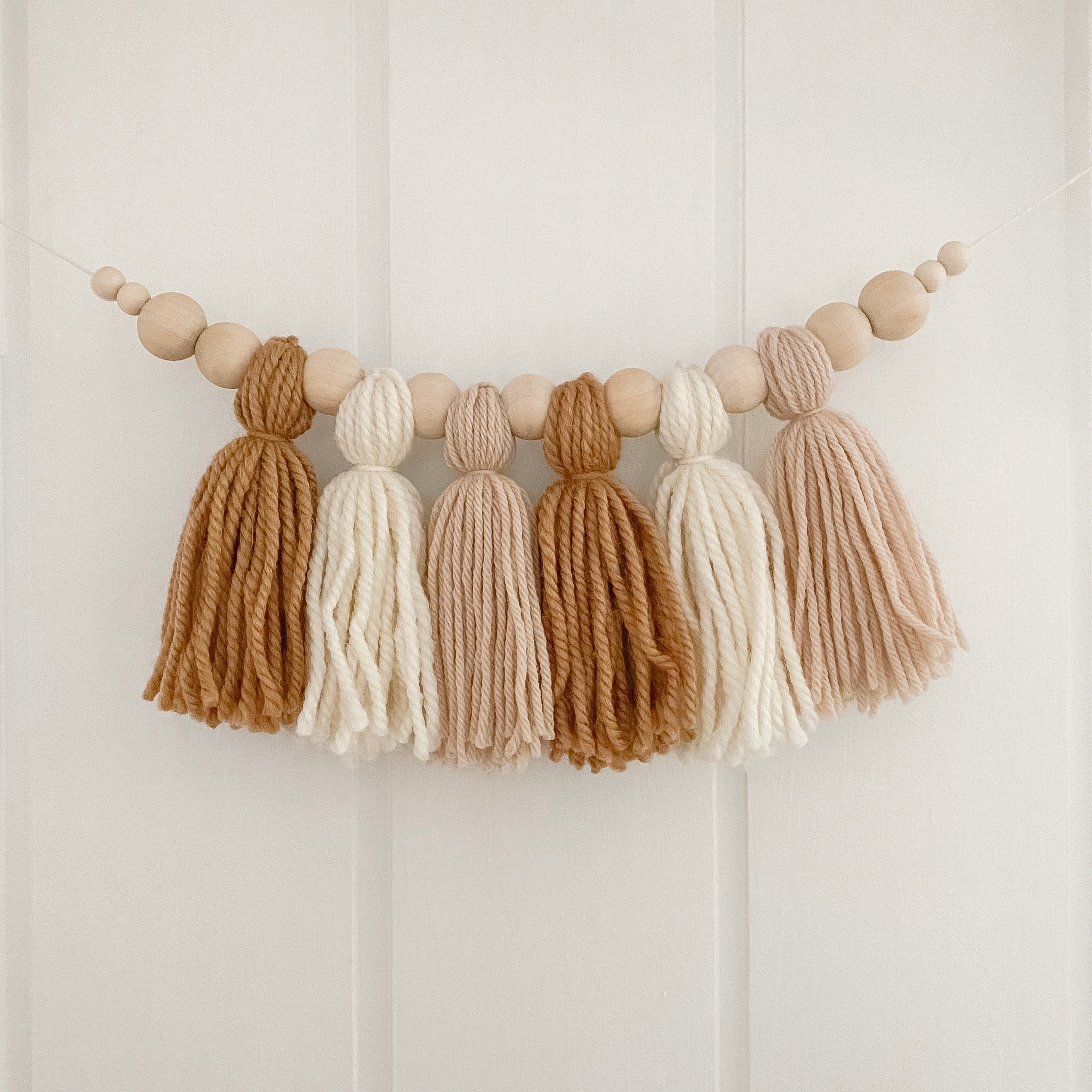 Neutral yarn tassel garland hanging on nursery wall