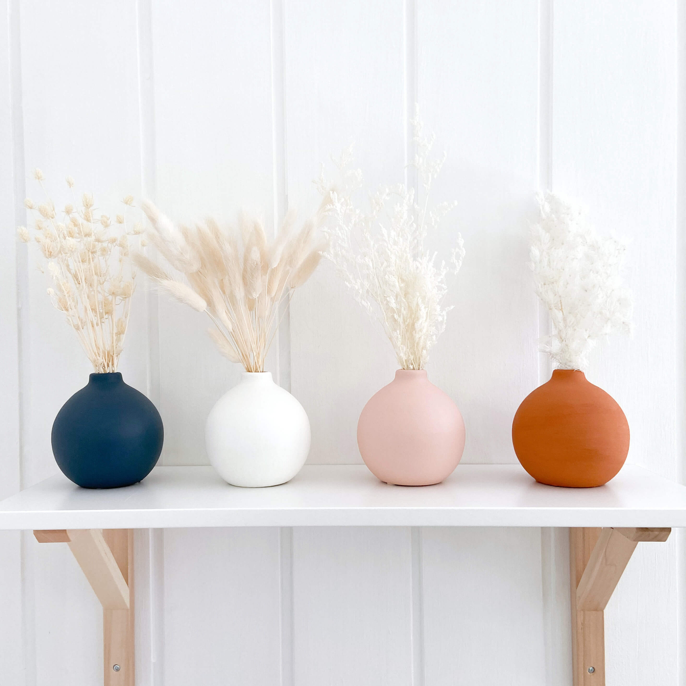 4 round vases in navy, pink, white and terracotta. Sitting on a white nursery shelf with dried bunny tails and preserved flowers in them