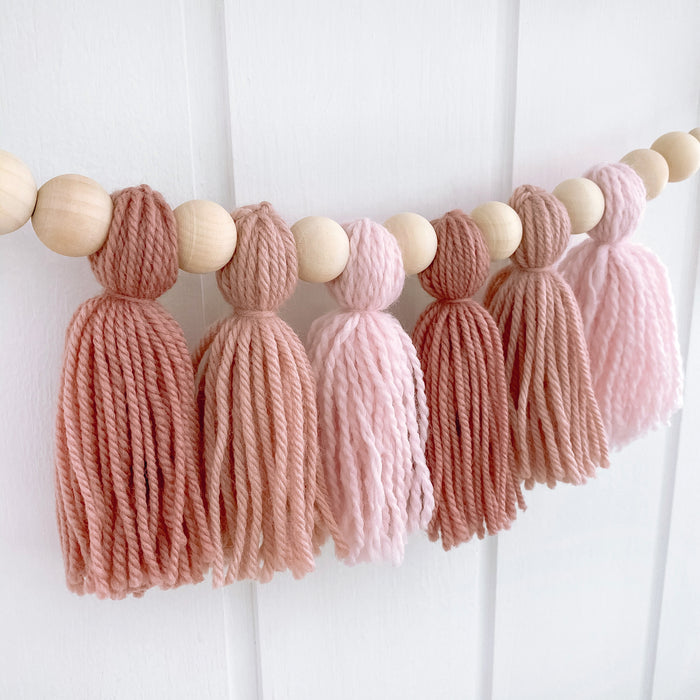 Close up of dusty pink tassel garland in girls baby room