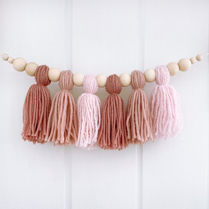 Dusty pink tassel garland hanging on girls bedroom wall