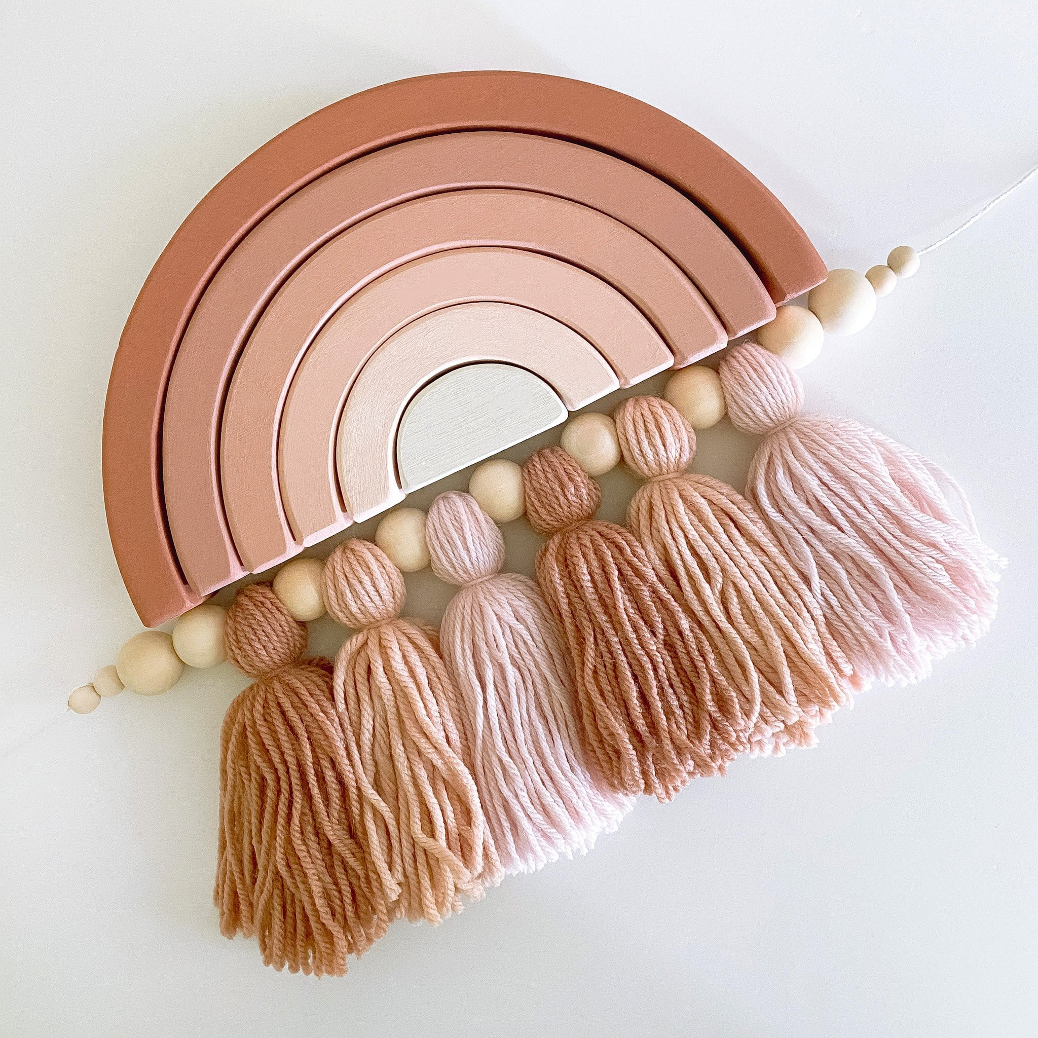 Earthy pink wooden rainbow sitting above a pink yarn tassel garland with beads