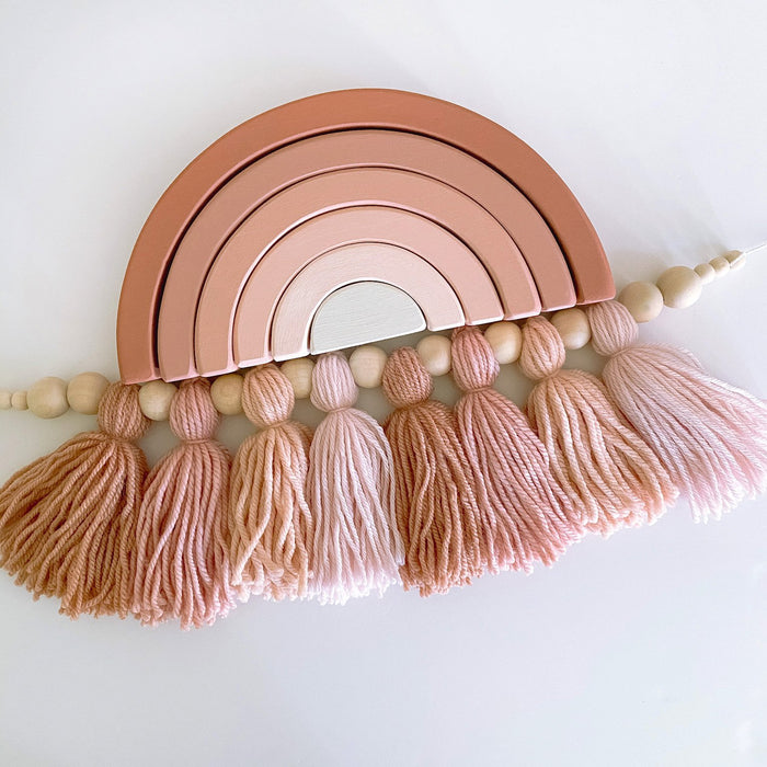 Wooden stackable rainbow toy and yarn tassel garland both in earthy pink ombre tones.