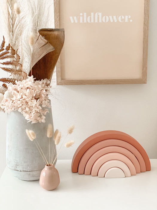 Styled girls room with pink decor. Earthy pink wooden rainbow, vases with preserved flowers and blush pink wild flower image framed above the decor pieces