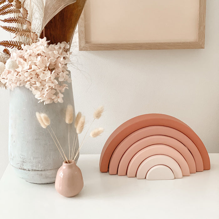 Styled shelf in girls bedroom with earthy pink wooden rainbow beside 2 vases with dried flowers. there is a blush pink framed image hanging on the wall