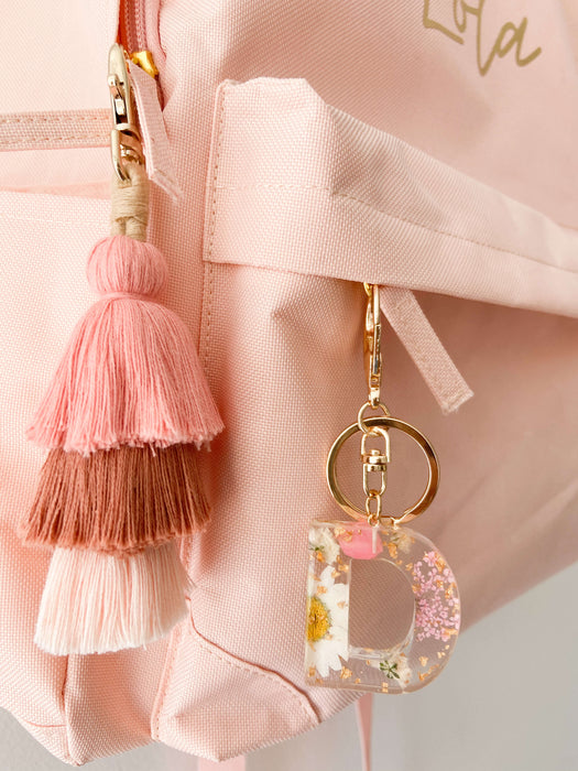 Pink and white flower resin keychain hanging on backpack with matching earthy pink tassel keychain