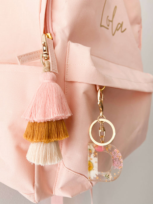 Pink and white flower resin keychain hanging on backpack with matching pink and mustard tassel keychain