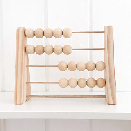 Handmade wooden abacus raw and natural sitting on nursery shelf