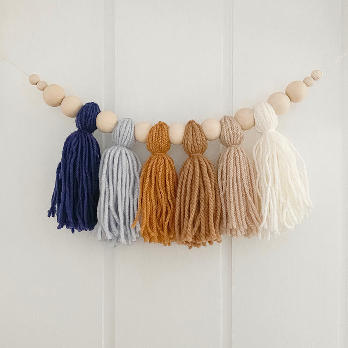 Navy and mustard yarn tassel garland hanging on boys nursery wall