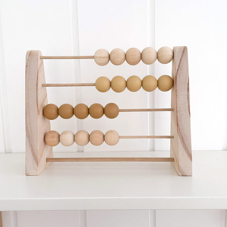 Handmade wooden abacus with neutral tones sitting on gender neutral nursery shelf