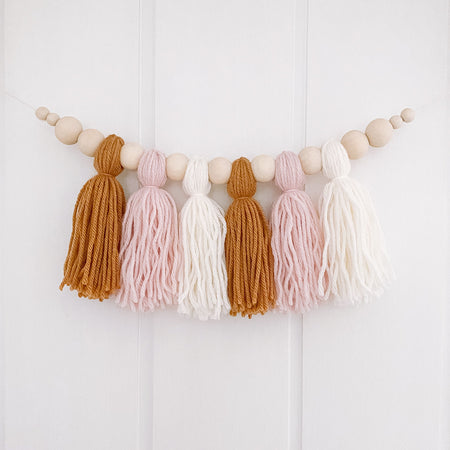 Yarn tassel garland in ochre, blush and cream hanging on kids wall