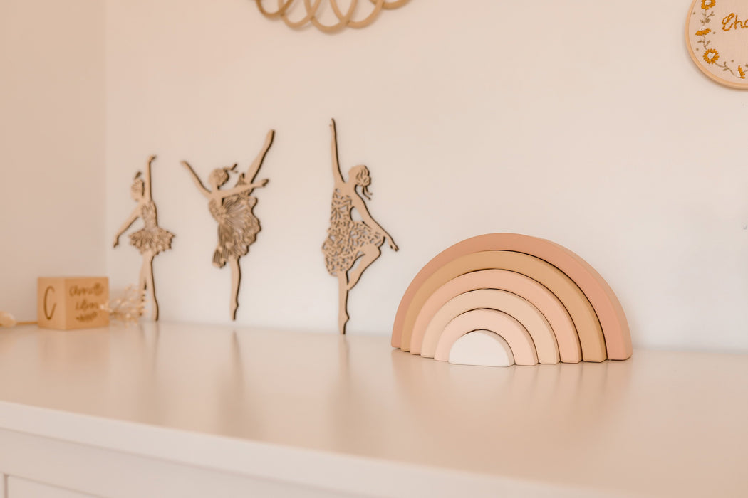 Girls bedroom styled in pink and beige. There is a wooden rainbow and timber ballerina cut outs against the wall