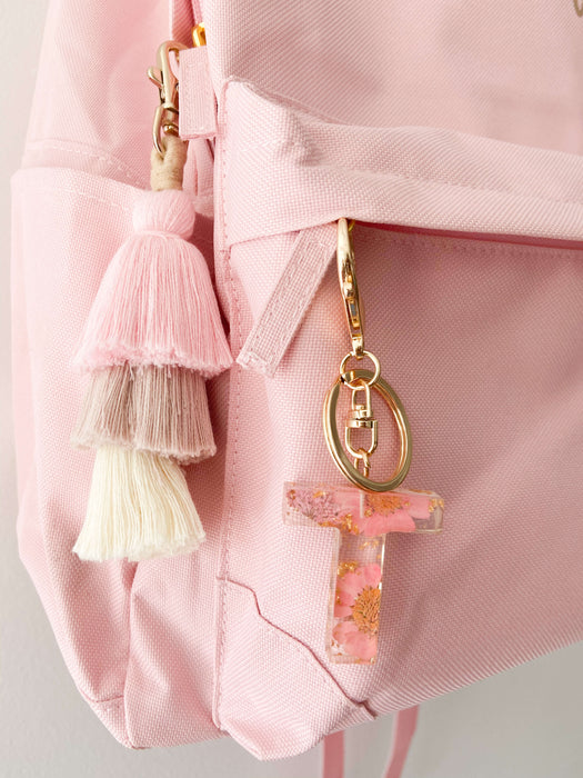 Pink letter keychain with dusty pink tassel keyring on kid's backpack