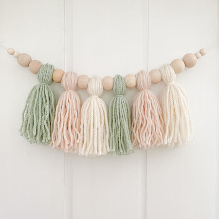 Handmade nursery wall garland. Sage, beige and cream tassels with beads are used