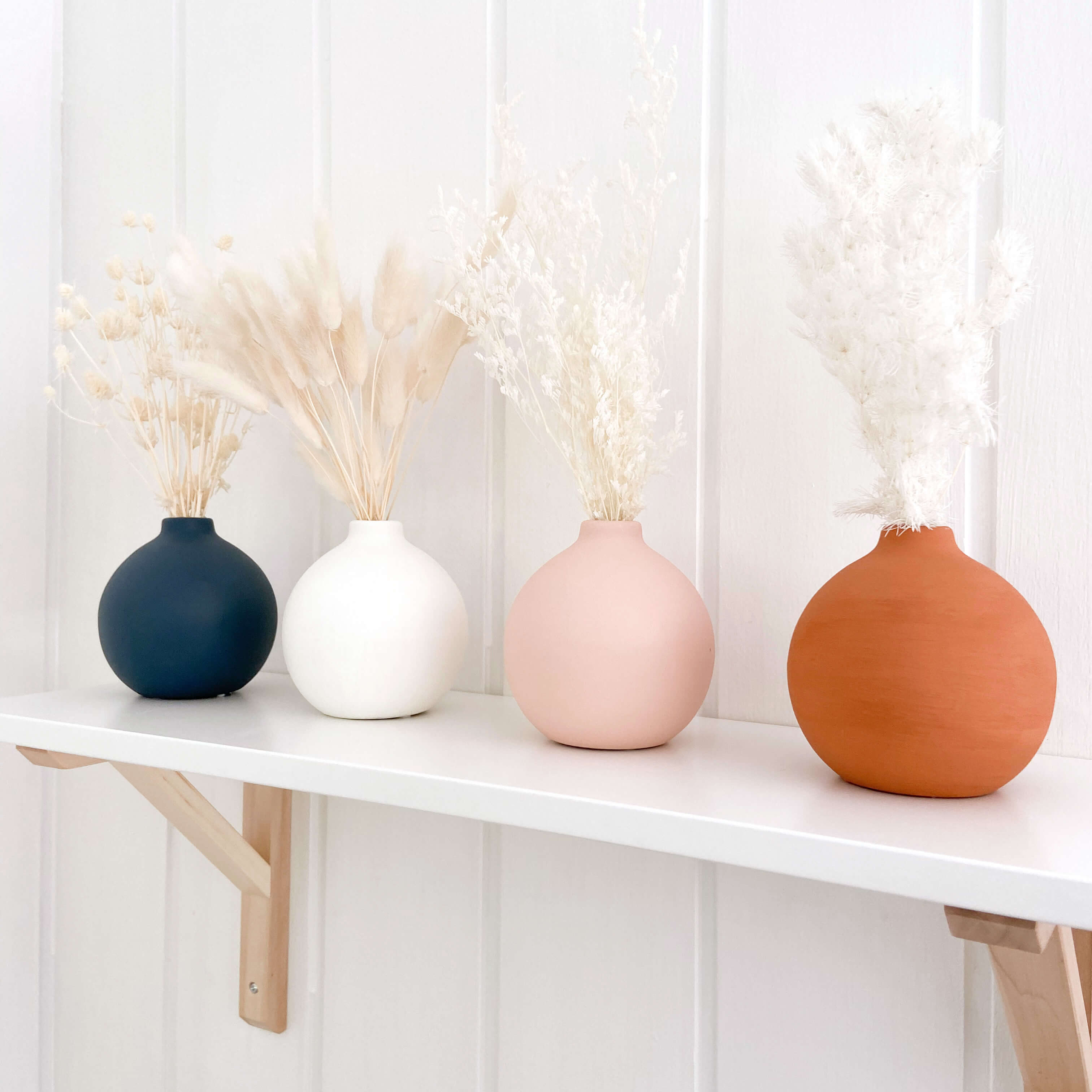 Kids nursery shelf with 4 vases sitting on it. They are navy, white, pink and terracotta. The vases have dried flowers in them
