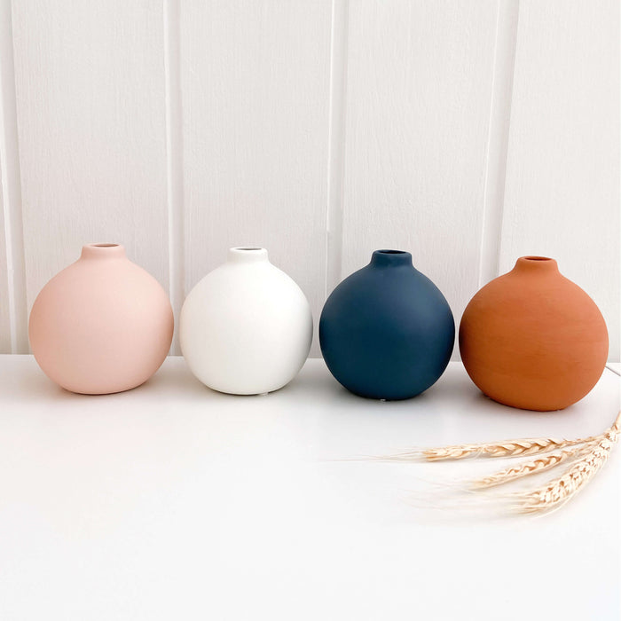 Four small round vases sitting on nursery shelf. The boho vases are in pink, white, navy and terracotta