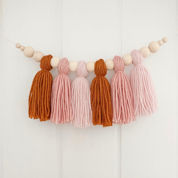Yarn tassel garland in tan, rose and blush hanging on nursery wall