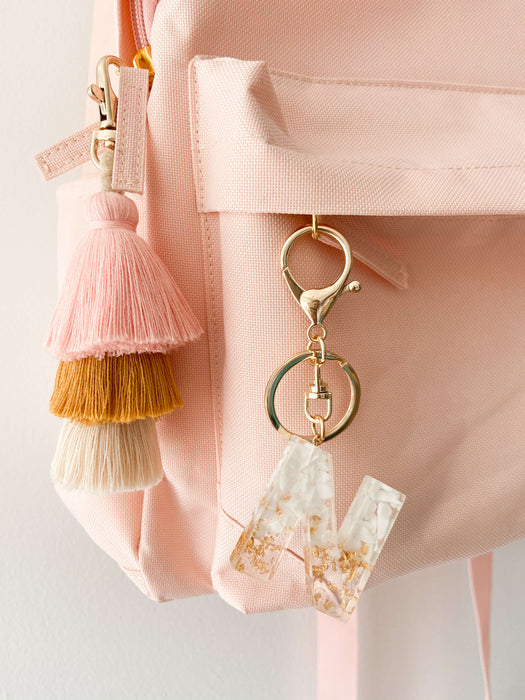 White resin letter keychain with pink and mustard tassel keyring hanging on personalised backpack