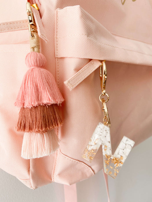 White resin letter keychain with earthy pink tassel keyring hanging on personalised kid's backpack