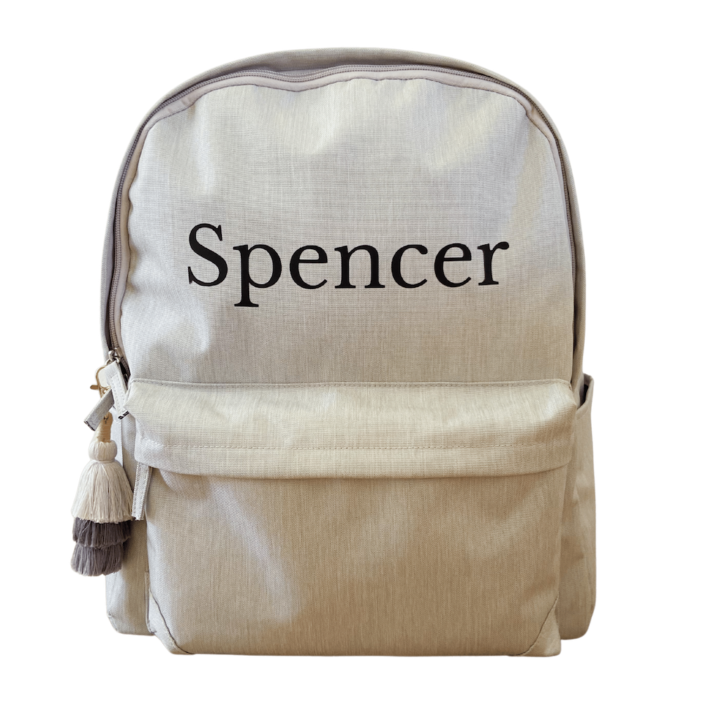 personalised kids backpack in light grey with tassel keychain and name in black