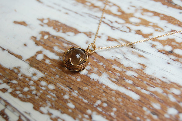 encased glass ball pendant | bronze