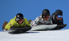 three people sliding down a snow hill