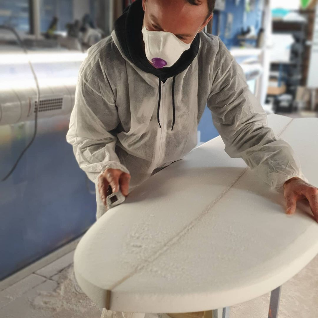 Marking out a surfboard template during a surfboard group course