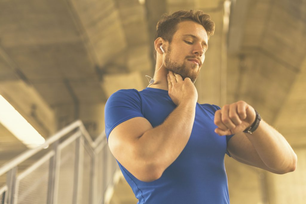 Man checking heart rate monitor on his fitness band