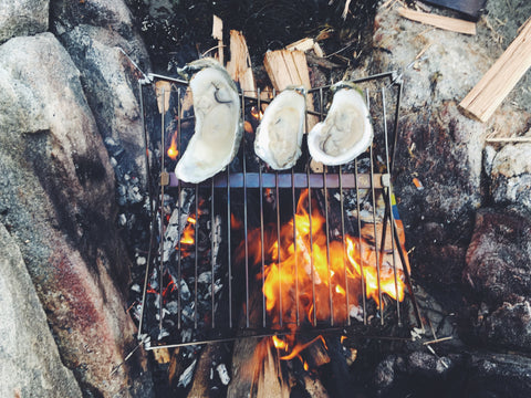 three oysters roasting on a grate over an open fire surrounded by Maine granite