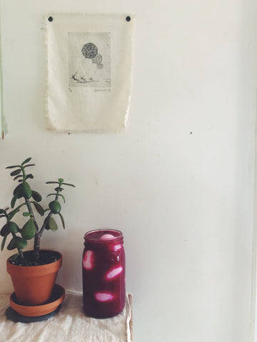 A mason jar of bright ruby pickled eggs sits next to a jade plant and an art print