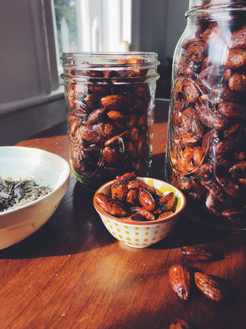 Jars of and bowls of roasted nuts glow in a beam of sunlight