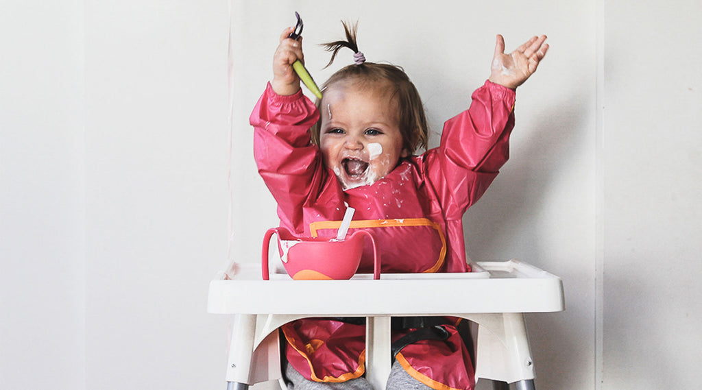 happy toddler using b.box smock bib and b.box bowl + straw on a high chair