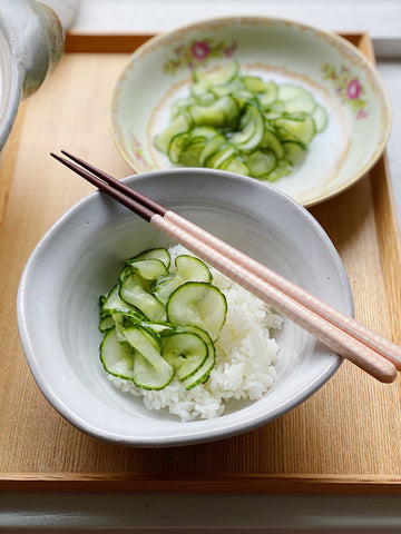 Pickled cucumbers over sushi rice with chopsticks