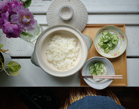 Donabe filled with rice and a bowl of pickled cucumbers over rice.