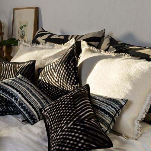 Aruba cushions with other Elitis Cushions on bed