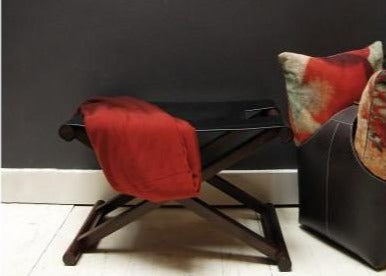 Black Leather Shikari Stool in home with red throw and cushions