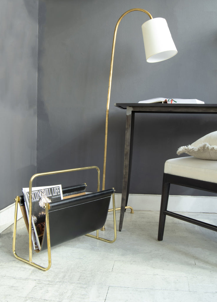 Magazine rack in corner with desk and lamp