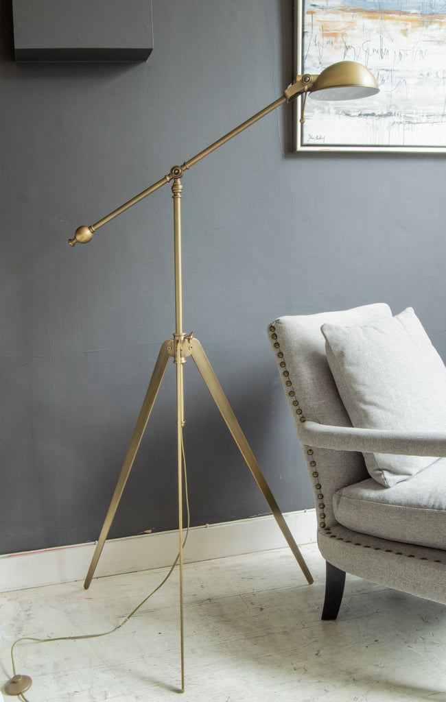 antique brass floor standing tripod lamp in home