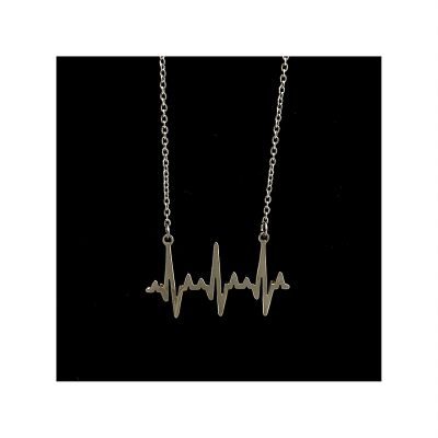 A silver cardiogram heartbeat necklace hanging in front of a black background